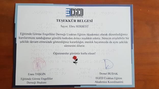"""Ebru SERBEST'e Ait teşekkür belgesi Betimlemesi: Etrafı açık koyu mavi çerçeve içersinde beyaz bir kuşe kağıt üzerinde, en üstte EGED  logosu, altında siyah yazı ile büyük harf ve büyük punto ile """"Teşekkür Belgesi"""" yazmakta. Haberde yer alan metnin altında kırmızı bir gül resmi var. Sağ altta Demet BUDAK'ın imzası,  solda ise Emre TAŞGIN'ın imzası ve kırmızı renkli dernek mühürü yer almakta."""
